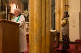 Father John gives a homile during mass, while his helper prays.