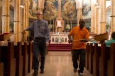Two parishioners carry collection baskets during the service.